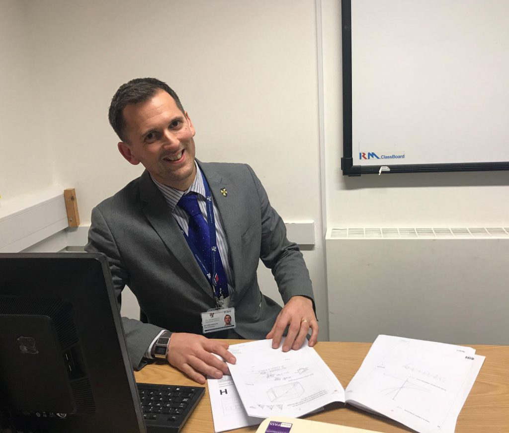 Matths teacher, Richard Brocklehurst, sat at his desk